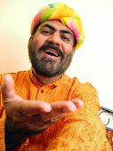 stock photo of rajasthani  - indian man in colotful rajasthani turban and long shirt called kurta in a happy mood - JPG