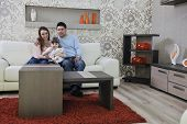 happy youg family relaxing in modern livingroom at home poster