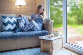 Young beautiful blonde woman with cup of coffee and book sitting home by the window. Summer spring g poster