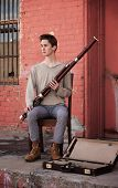 image of sounding-rod  - Young Caucasian man with Bassoon sitting on a wooden chair outside - JPG