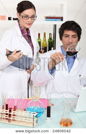 Two scientist with wine in laboratory