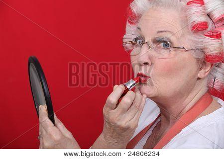 Old lady applying lipstick