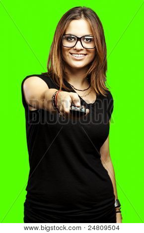 portrait of young woman using tv remote control against a removable chroma key background