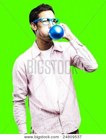 portrait of young man blowing a balloon against a removable chroma key background