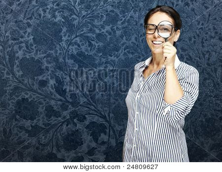 portrait of a middle aged woman looking through a magnifying glass against a vintage wall