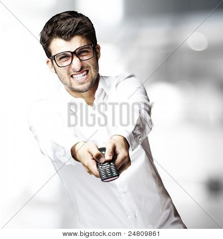 portrait of young man changing channel with tv control indoor