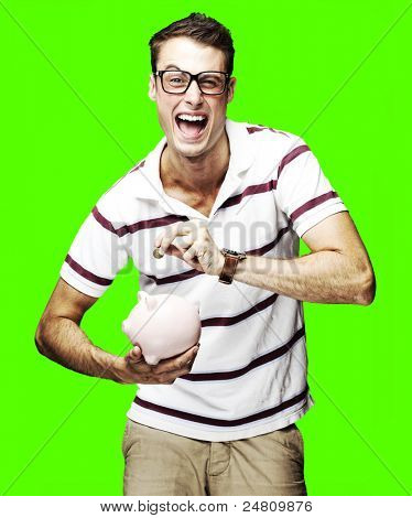 portrait of a crazy young man holding a piggy bank over a removable chroma key background