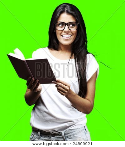 portrait of young woman holding book against a removable chroma key background