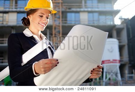 Young Female Architect/construction Engineer Reviewing Plans At A Construction Site