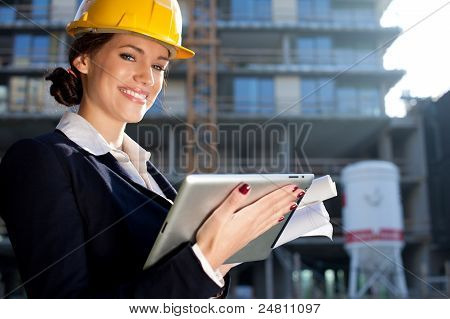 Attractive Happy Female Construction Engineer/architect With A Tablet Computer At A Construction Sit