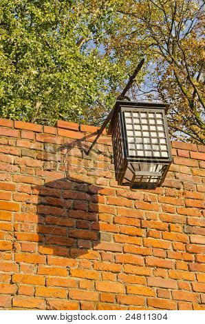 Ancient Illuminator Mounted On Red Brick Wall. Oldtown Details.