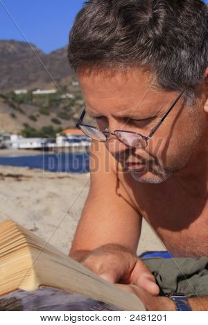 Middle Aged Man Reading A Book At The Beach