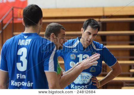 KAPOSVAR, HUNGARY - OCTOBER 29: Gyorgy Demeter (C) in action at a Hungarian National Championship volleyball game Kaposvar (blue) vs. Szolnok (red), October 29, 2011 in Kaposvar, Hungary.