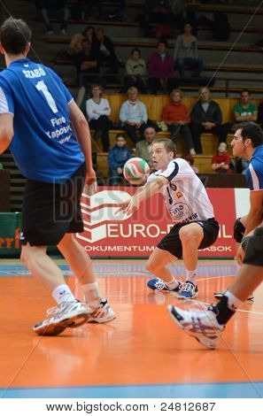 KAPOSVAR, HUNGARY - OCTOBER 29: Lajos Domotor (in white) in action at a Hungarian National Championship volleyball game Kaposvar (blue) vs. Szolnok (red), October 29, 2011 in Kaposvar, Hungary.