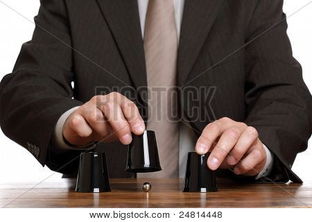 Businessman performing shell game scam with cups concept for corporate theft, chance, choice or making decisions