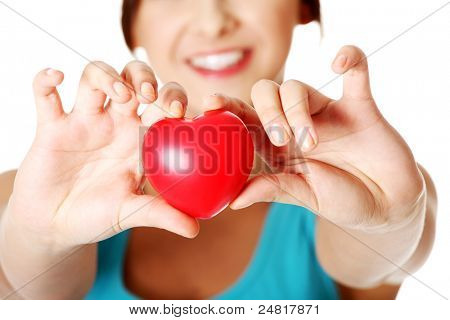 Pretty teen girl showing red heart in her hand over white.