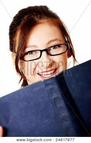Closeup portrait of smiling, caucasian, teen student with a blue book over white.