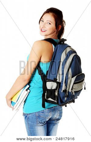 Young beautiful caucasian teen student with notes smiling and showing her backpack. Isolated on white.