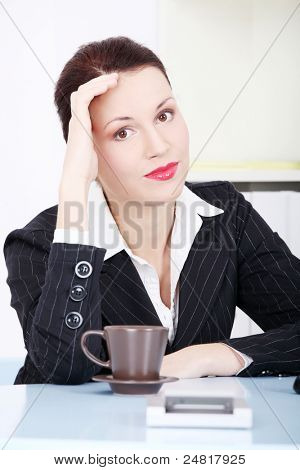Pretty caucasian thinking businesswoman sitting behind the desk in the office.