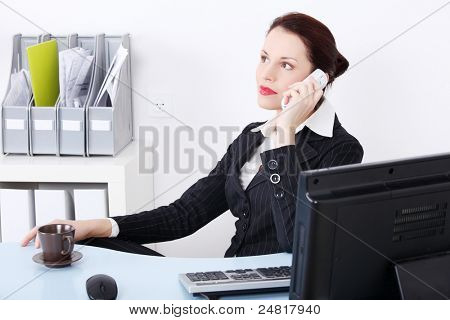 Pretty caucasian businesswoman answering the phone in the office.