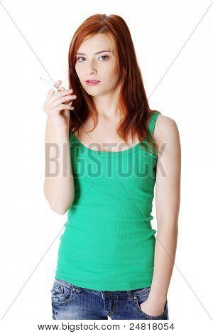 Teen girl bastante caucásica de pie sosteniendo el cigarrillo.