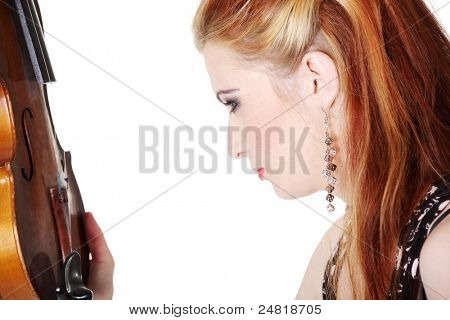 Close-up portrait of teen girl looking at fiddle.