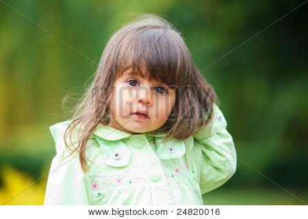 little girl in green walking park.