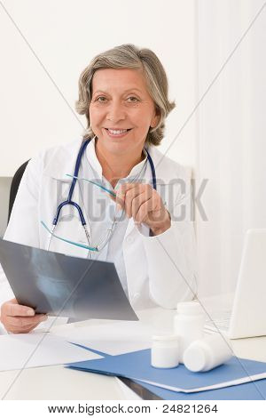 Senior Doctor Female Sit Behind Office Desk