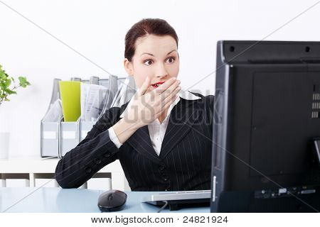 Surprised beautiful caucasian businesswoman looking at the computer and sitting behind the desk in the office.