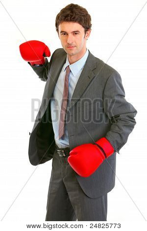 Serious Modern Businessman In Boxing Gloves Brandishing To Attack