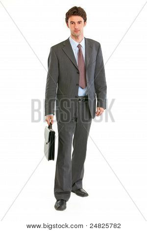 Confident Modern Businessman With Suitcase Making Step