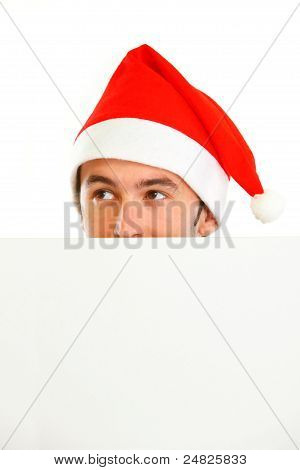 Hiding In Front Of Blank Billboard Guy In Santa Hat Looking In Corner