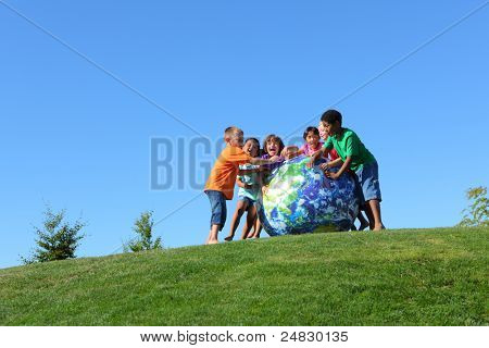 Kids with large earth ball, on grass hill with blue sky