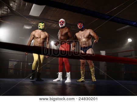 Three masked wrestlers stand in ring