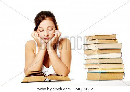 Chica bonita caucásica joven sentado y leyendo un libro junto a la pila de libros.