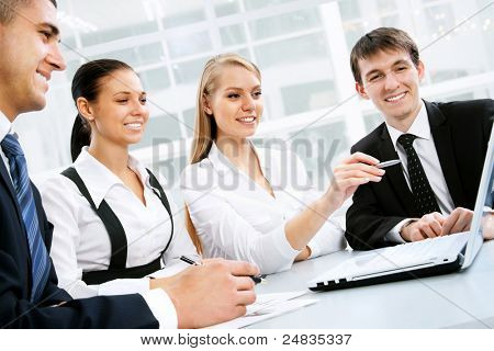 Photo of business people looking at laptop monitor