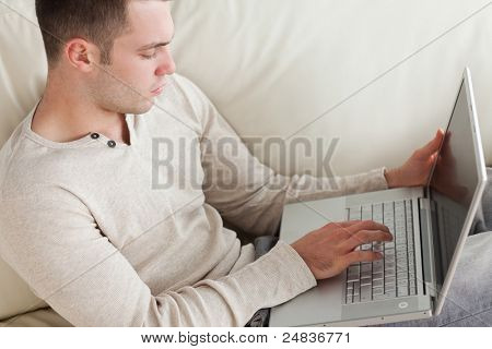 Good looking man relaxing with a laptop in his living room