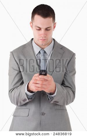 Portrait of a businessman dialing on his cellphone against a white background
