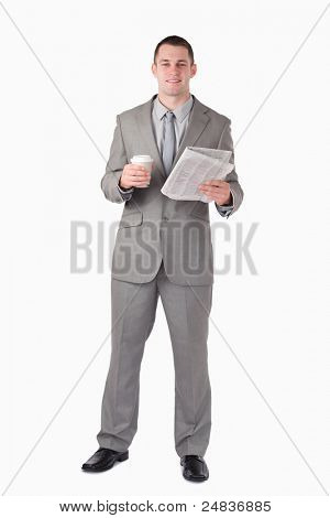 Portrait of a businessman holding a newspaper and a cup of coffee against a white background