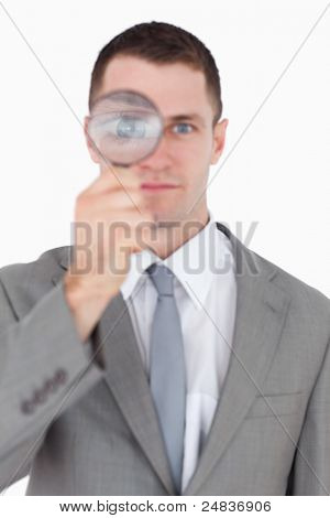 Portrait of a businessman looking through a magnifying glass against a white background