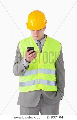 Portrait of a young builder looking at his cellphone against a white background