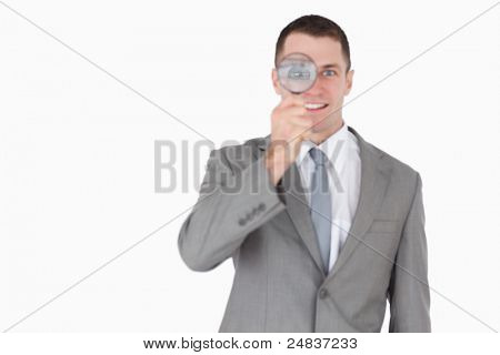 Businessman looking through a magnifying glass against a white background