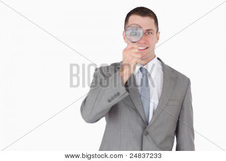 Empresario mirando a través de una lupa sobre un fondo blanco