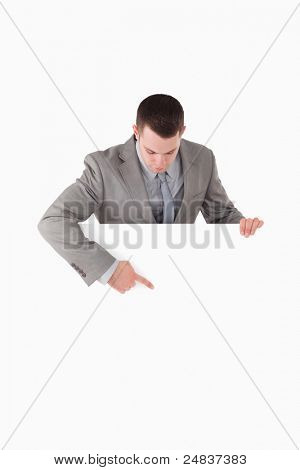 Portrait of a businessman pointing at something on a panel against a white background