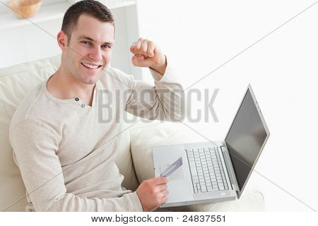 Young man shopping online with the fist up in his living room