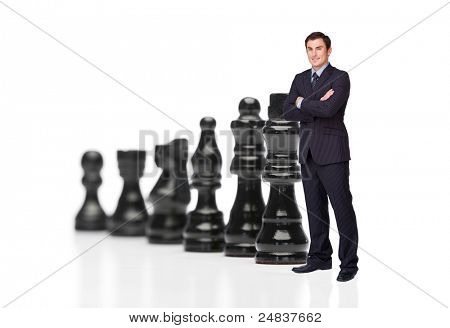Businessman in front of black chess pieces