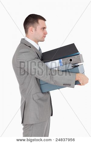Portrait of a businessman holding a stack of binders against a white background