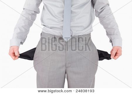 Businessman showing his empty pockets against a white background