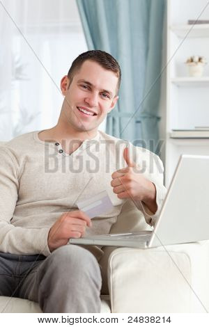 Portrait of a man shopping online with the thumb up in his living room