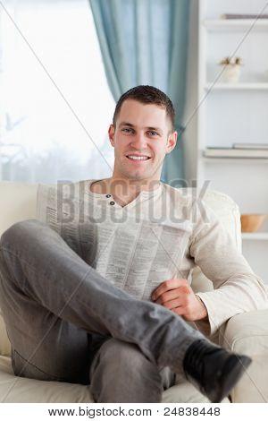Retrato de un hombre sonriente, leyendo un periódico en su sala de estar